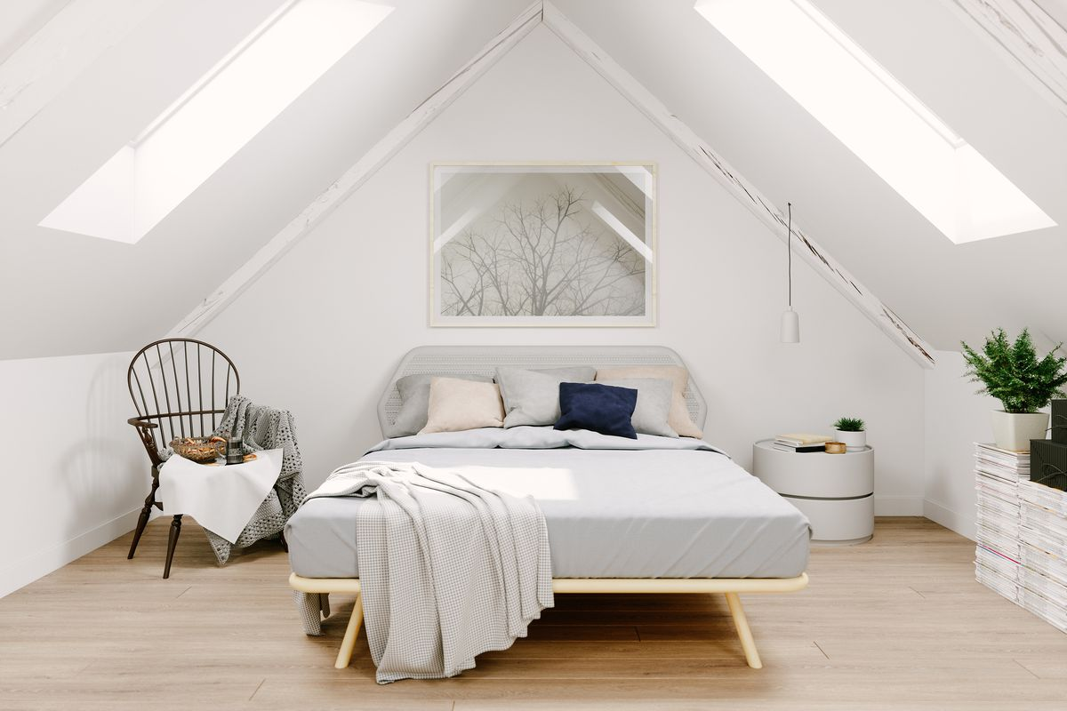 Interior of a Scandinavian style attic bedroom with a monochromatic (white/light gray) color scheme. There are two large skylights on the ceiling that allow for a lot of natural light.