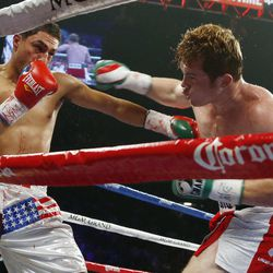 Canelo Alvarez, of Mexico, right, punches Josesito Lopez during a super welterweight championship boxing match on Saturday, Sept. 15, 2012, in Las Vegas. Alvarez won the match.