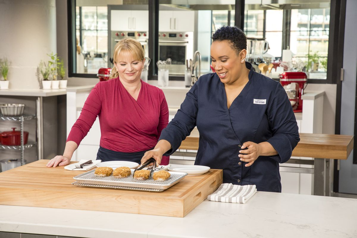 Elle Simone Scott uses tongs to pick up a crab cake on the set of America's Test Kitchen.