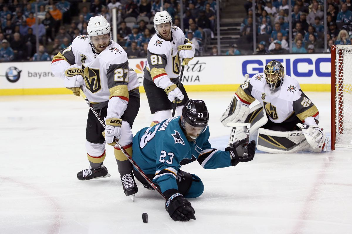 SAN JOSE, CA - APRIL 30: Shea Theodore #27 of the Vegas Golden Knights and Barclay Goodrow #23 of the San Jose Sharks go for the puck during Game Three of the Western Conference Second Round during the 2018 NHL Stanley Cup Playoffs at SAP Center on April