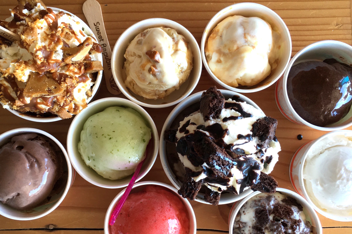 Various ice cream flavors arranged in cups with wooden Sweet Republic spoons on a table.