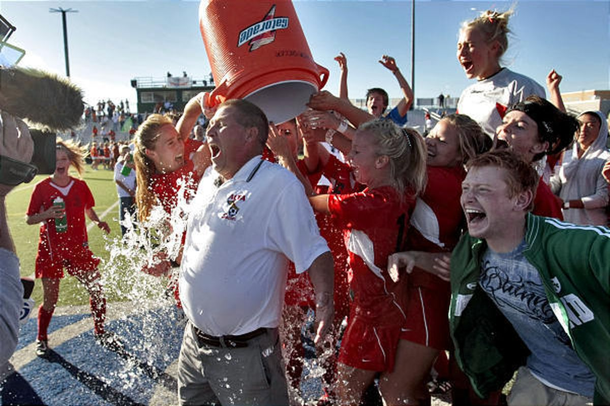 Alta coach Lee Mitchell gets dowsed by his team after Hawks beat Brighton 2-0 to claim their third 5A soccer championship in a row.