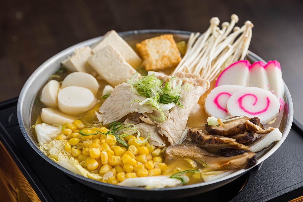A hot pot on a burner with yellow curry broth, fish cakes, mushrooms, and chicken