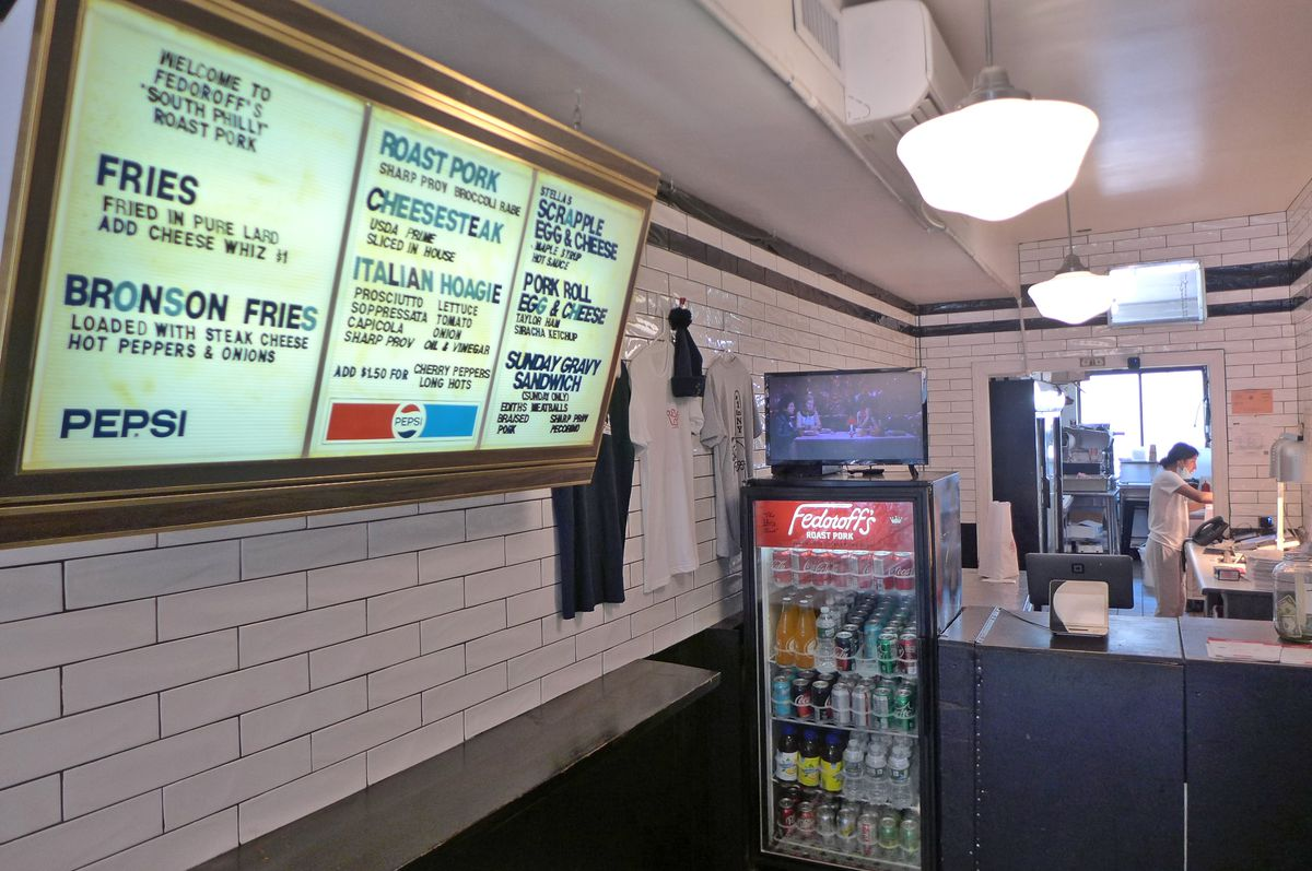 A white tiled space with an illuminated menu on it, and an order counter at the end.