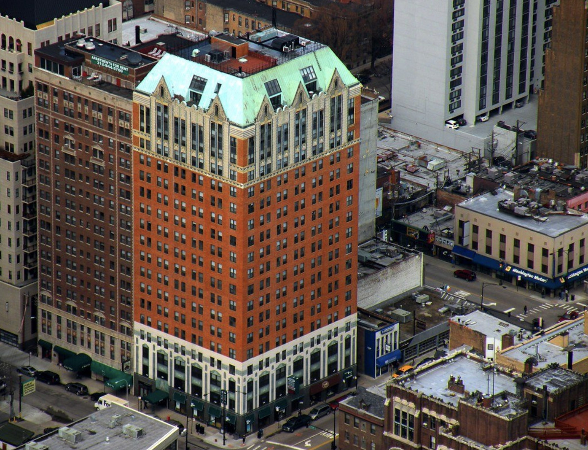 A bird's eye view of the large apartment building. It has brick and a teal roof.