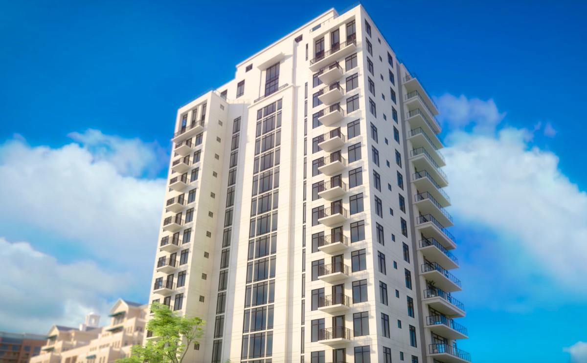 A white condo tower set against a blue sky.