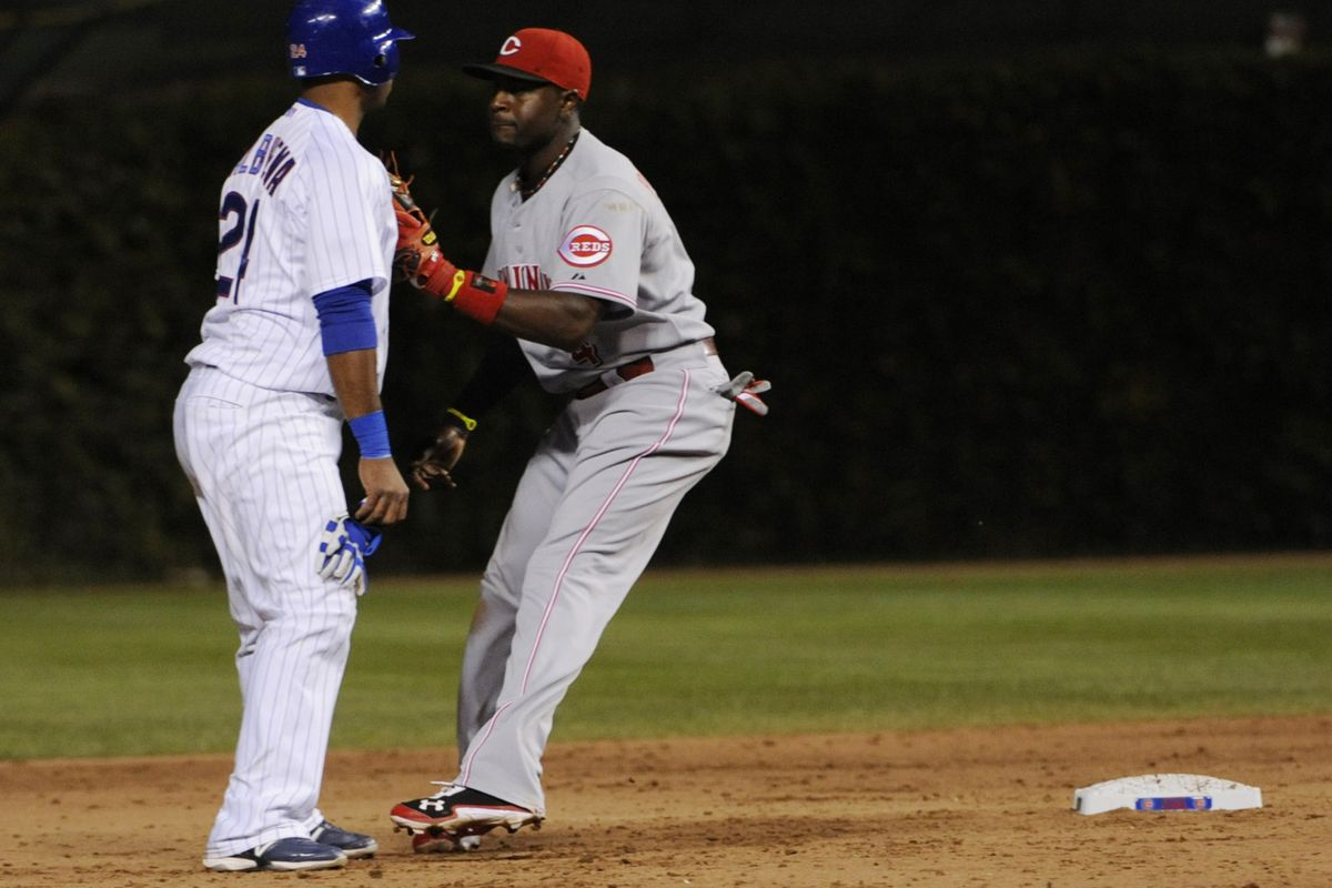 Luis Valbuena of the Chicago Cubs is picked off of second base and is tagged out by Brandon Phillips of the Cincinnati Reds at Wrigley Field in Chicago, Illinois.  (Photo by David Banks/Getty Images)