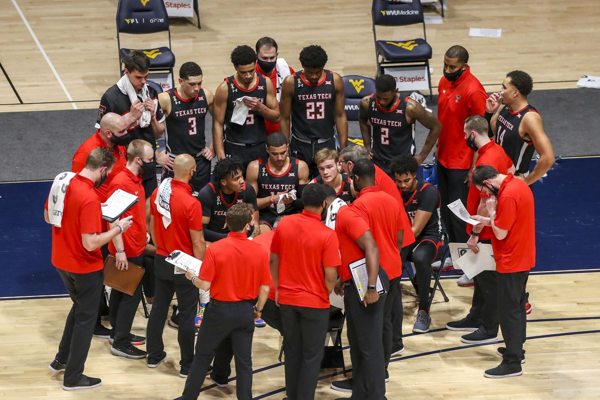 Texas Tech Red Raiders players listen to Texas Tech Red Raiders head coach Chris Beard during a timeout during the second half against the West Virginia Mountaineers at WVU Coliseum.