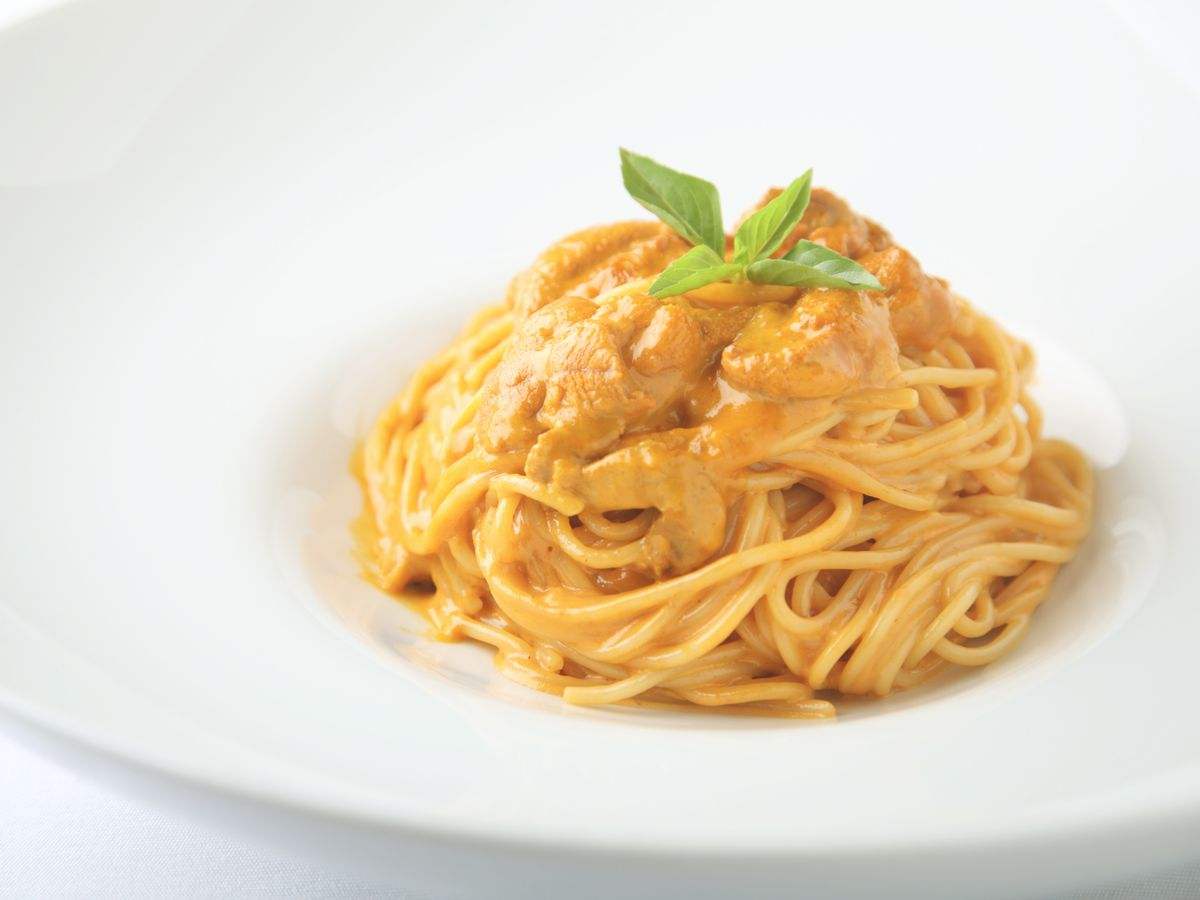 A pile of spaghetti with thick sea urchin sauce and a small basil leaf for garnish