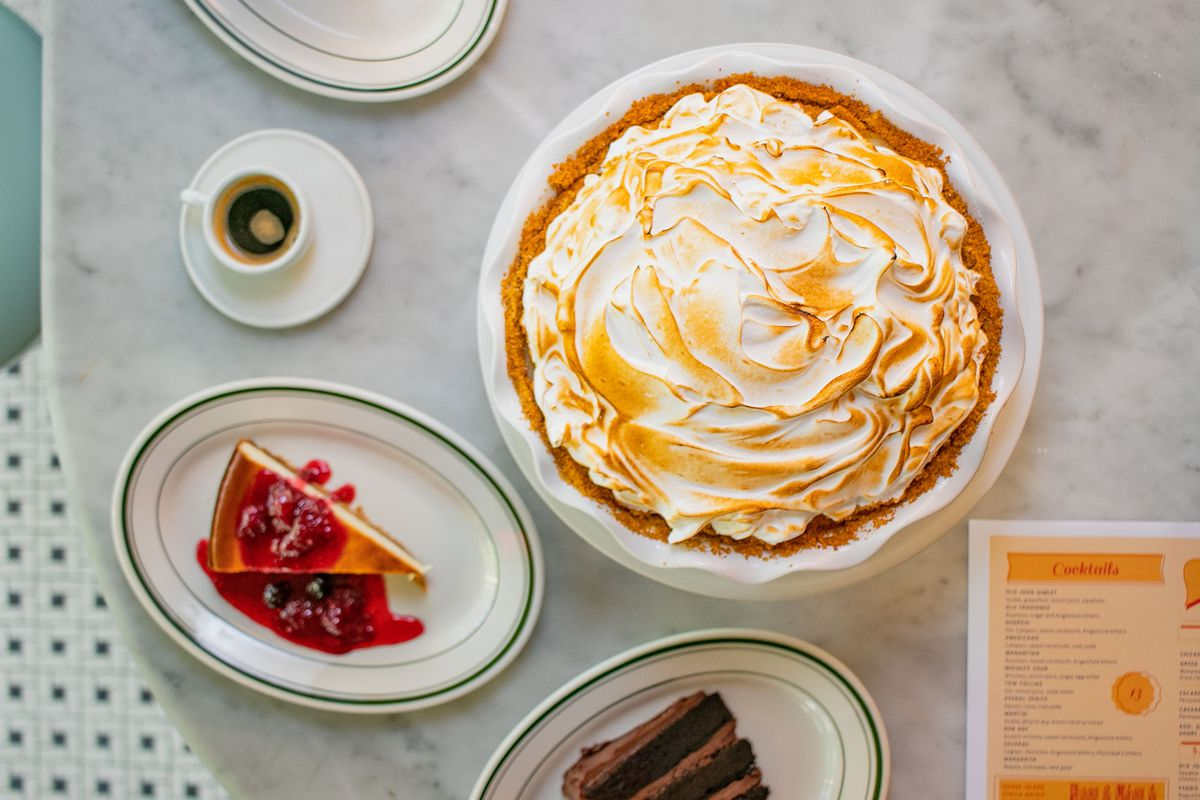 A whole pie sits on a white cake stand with slices of cheesecake, chocolate cake, and a small espresso cup surrounding it on a white marble table