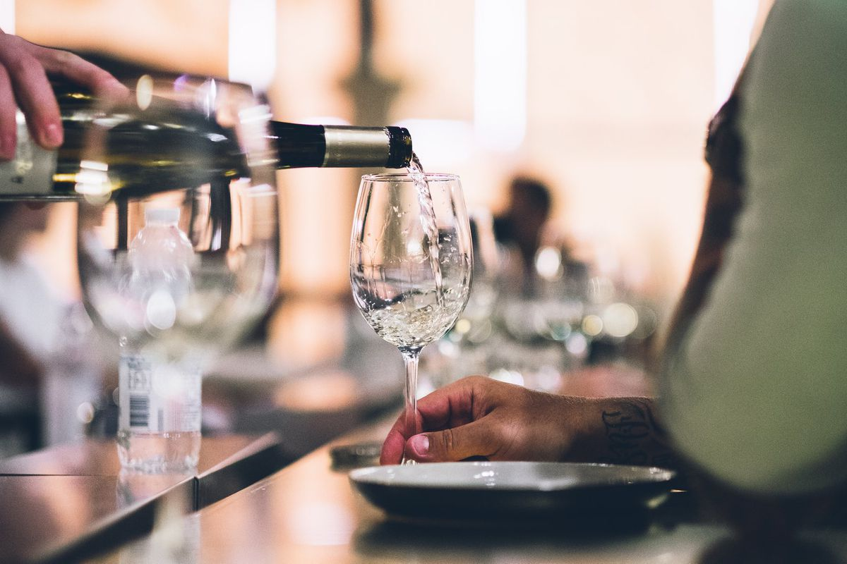 White wine being poured from a bottle into a glass, while somebody holds the glass at its stem.