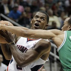 Atlanta Hawks' Joe Johnson, left, handles the ball in front of Boston Celtics' Avery Bradley during the second quarter of Game 1 of an opening-round NBA basketball playoff series, Sunday, April 29, 2012, in Atlanta.