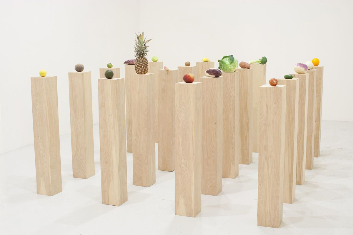 Several wooden pedestals hold various fruits and vegetables atop them as part of a museum exhibit at the Whitney Museum.