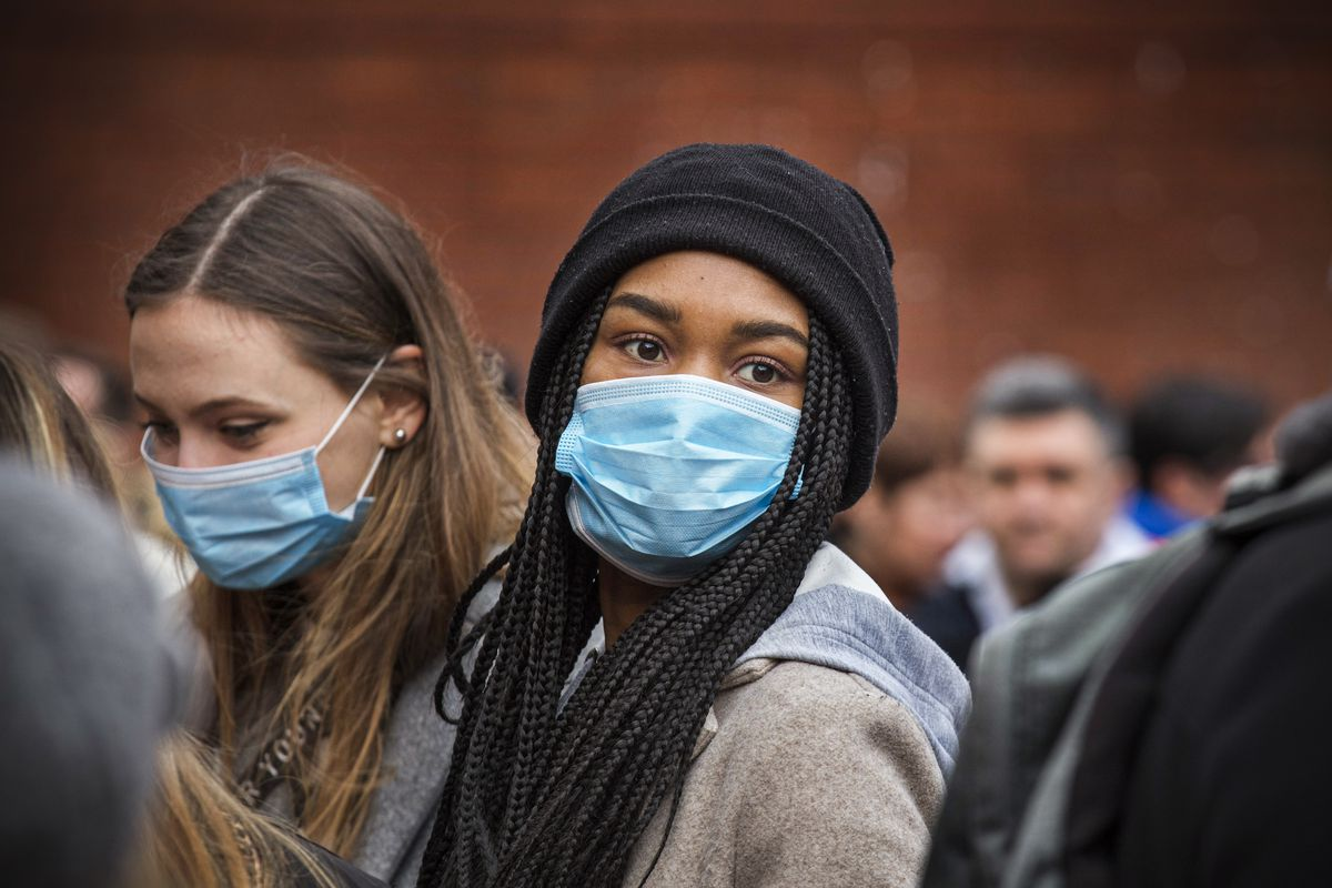 Young women wear masks as protection against the coronavirus