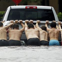 People push a stalled pickup through a flooded street in Houston, after Tropical Storm Harvey dumped heavy rains, Sunday, Aug. 27, 2017. The remnants of Harvey sent devastating floods pouring into Houston on Sunday as rising water chased thousands of people to rooftops or higher ground.