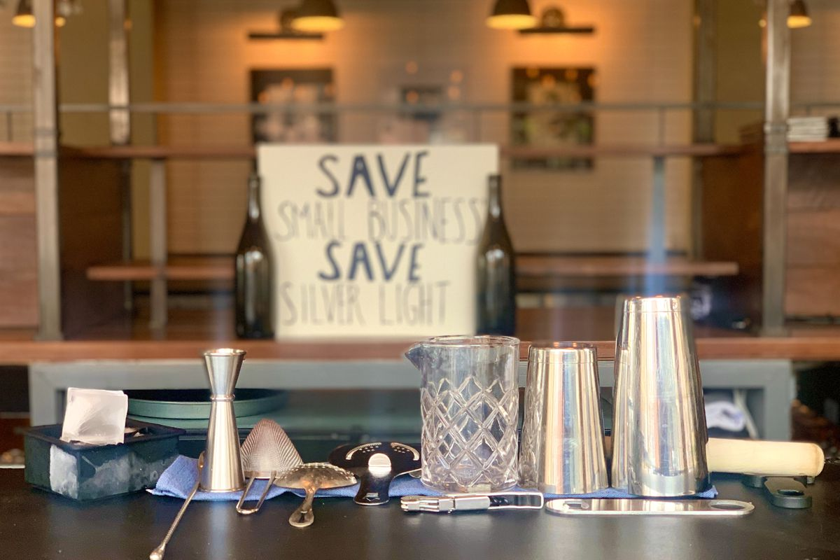 """Cocktail-making tools spread out on a table in front of a sign that reads """"Save Small Business, Save Silver Light"""" in the background"""