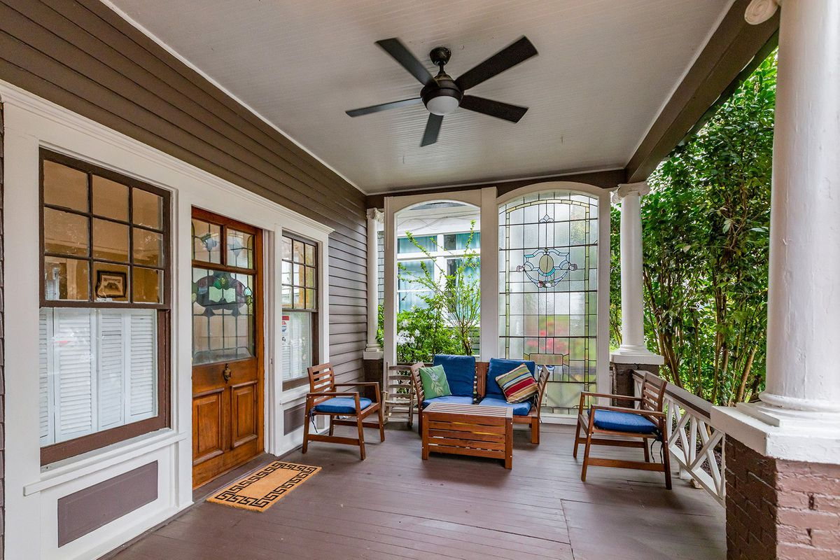 A porch sitting area with a ceiling fan overhead.