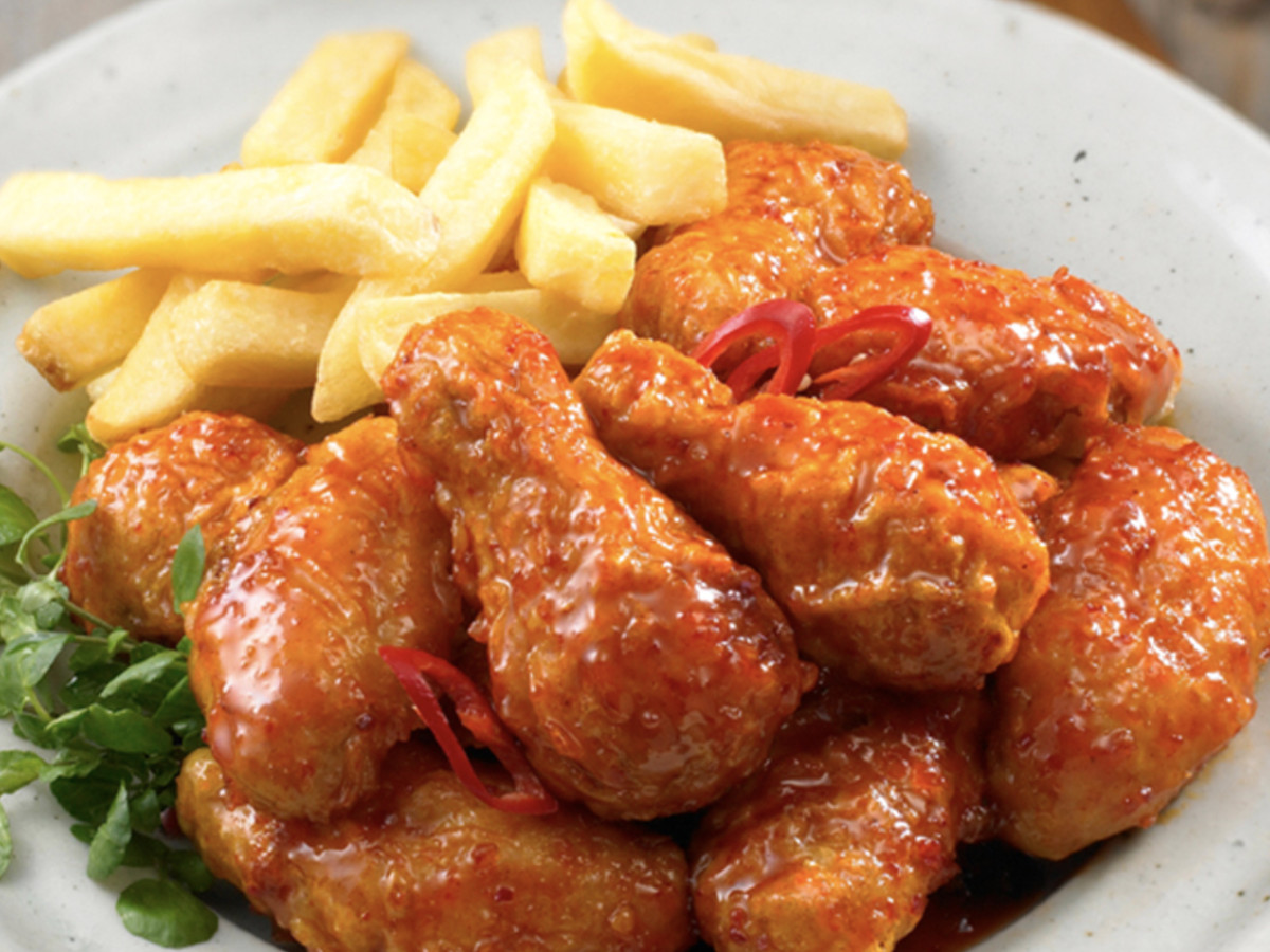 A plate of spicy chicken wings with a side of fries