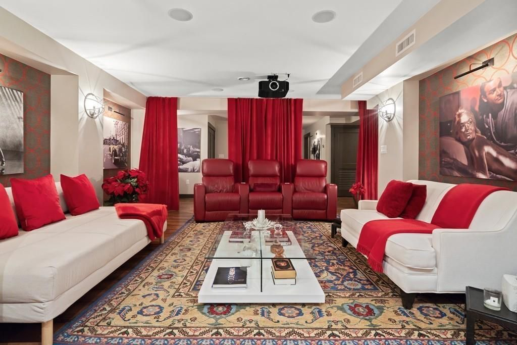 A home theater with three chairs between two couches that are facing each other.