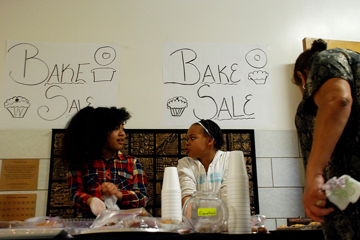 Carmen Stevens, left, and Amarria Miller volunteer at their classroom's bake sale in December 2015. The Gilpin Montessori students were raising funds for their class pets.