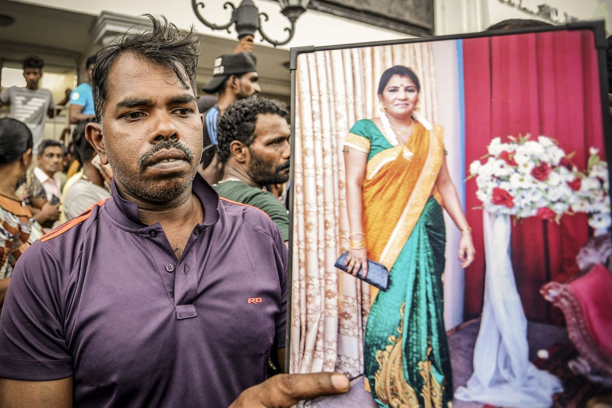 A Sri Lankan Catholic man holds a photograph of his sister while waiting to identify her dead body in front of St. Anthony's Church.