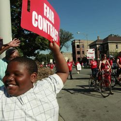 A young boy holds a placard in support of striking Chicago school teachers as they march after a rally Saturday, Sept. 15, 2012 in west Chicago.
