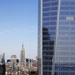 """FILE - In this April 17, 2012, file photo, One World Trade Center, right, rises above the  Manhattan skyline and the Empire State Building, center, in New York. One World Trade Center, the giant monolith being built to replace the twin towers destroyed in the Sept. 11 attacks, will lay claim to the title of New York City's tallest skyscraper on Monday, April 30 as workers erect steel columns that will make its unfinished skeleton a little over 1,250 feet, just high enough to peak over the observation deck on the Empire State Building, center. The milestone is a preliminary one. The so-called """"Freedom Tower"""" isn't expected to reach its full height for at least another year, at which point it is likely to be declared the tallest building in the U.S."""