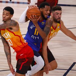 Monte Morris, center, of the Denver Nuggets, drives between Jordan Clarkson, left, and Georges Niang, right, of the Utah Jazz during the first half of Game 4 of an NBA basketball first-round playoff series, Sunday, Aug. 23, 2020, in Lake Buena Vista, Fla.