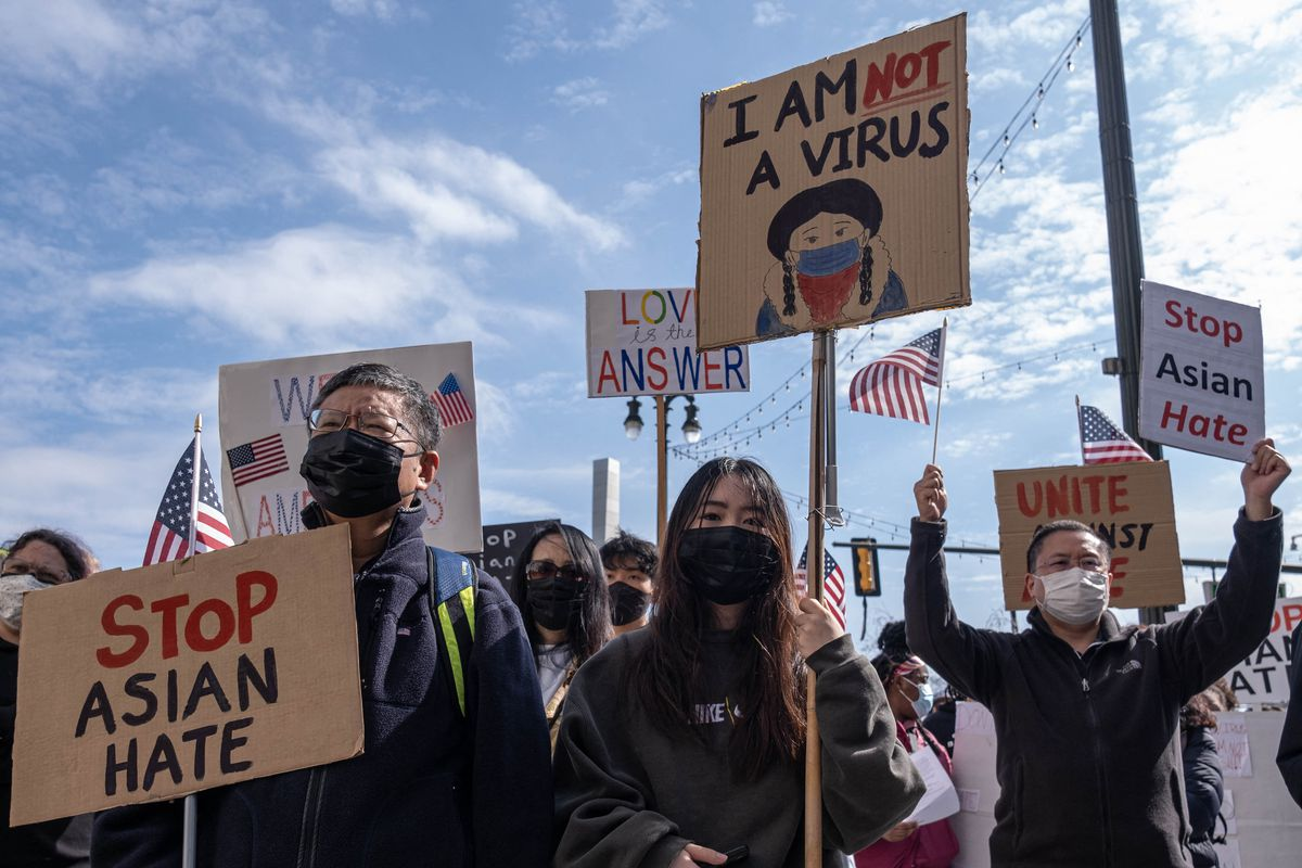 """People at a protest hold signs that read """"I am not a virus,"""" and """"Stop Asian Hate."""""""