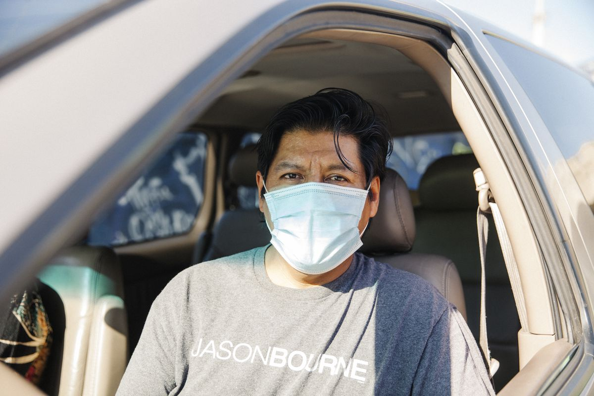 Man wearing disposable mask looks directly at the camera from the front seat of his car.