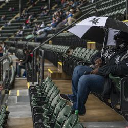 Chicago White Sox fan Terri Williams-Brown, waits under her umbrella for the game to begin at Guaranteed Rate Field during the White Sox home opener against the Kansas City Royals, Thursday, April 8, 2021.