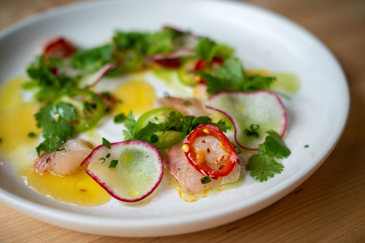 A closeup view of black cod ceviche with green herbs, red peppers, shaved radishes, and a yellow sauce.