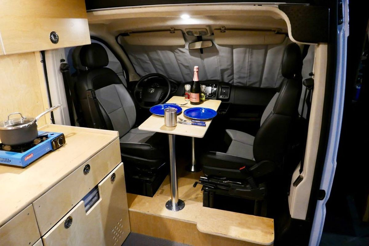 The interior of a camper van. There are black seats, a wooden table, and a kitchenette with a portable stove.