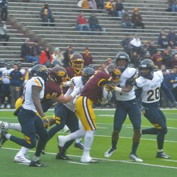 Multiple Toledo defenders attempt to take down Jonathan Ward on a run for first down.