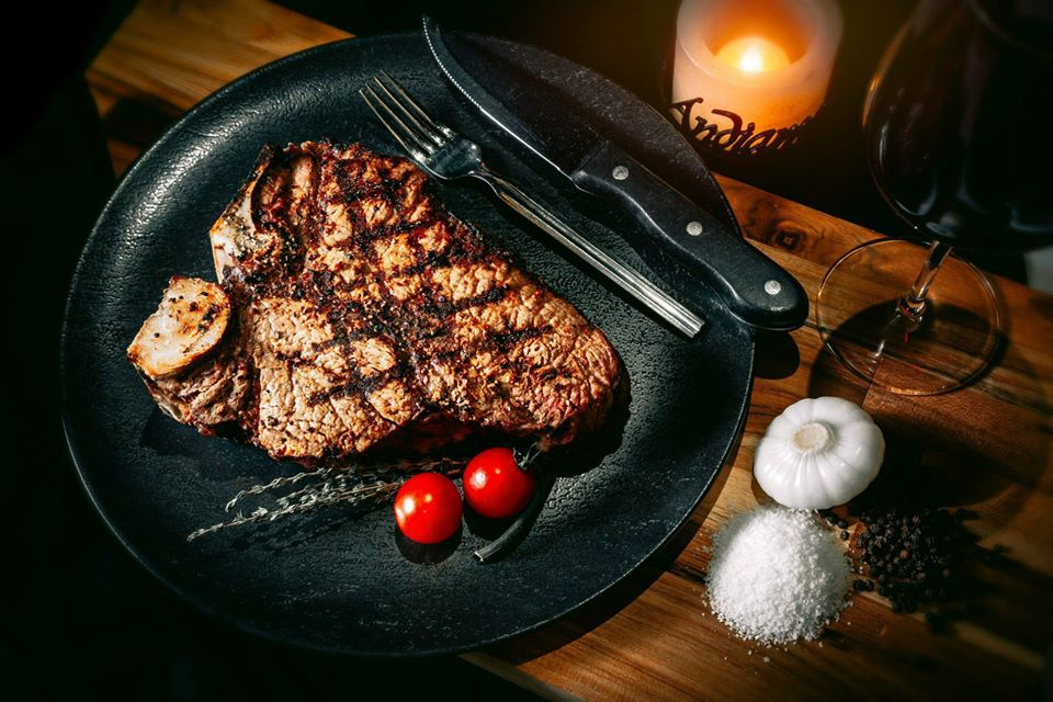 Steak on black plate alongside garnishes