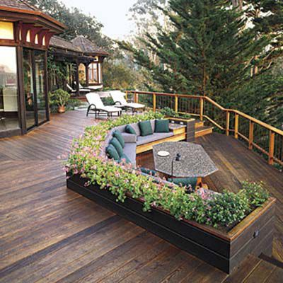 A wooden deck with plant container boxes and outdoor seating.
