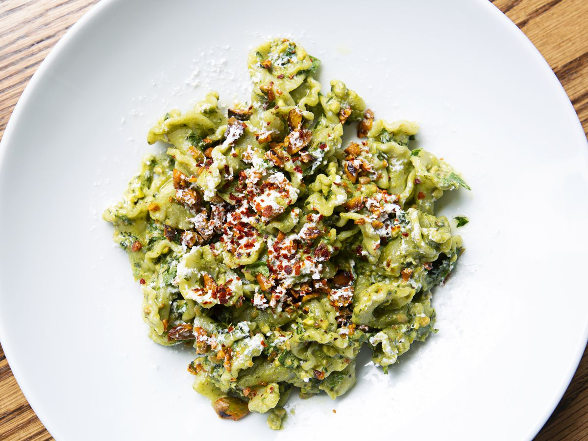 Overhead view of a round white plate filled with bright green twists of pasta.