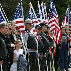 People line the sidewalk holding American flags during the military funeral   for Civil War veteran Peter Knapp at Willamette National Cemetery in Portland, Ore., Friday, April 13, 2012.  Peter Knapp is the first Civil War veteran buried at Willamette National Cemetery, Oregon's largest veterans' cemetery. His ashes had been sitting on a shelf at the Portland Crematorium since 1924.