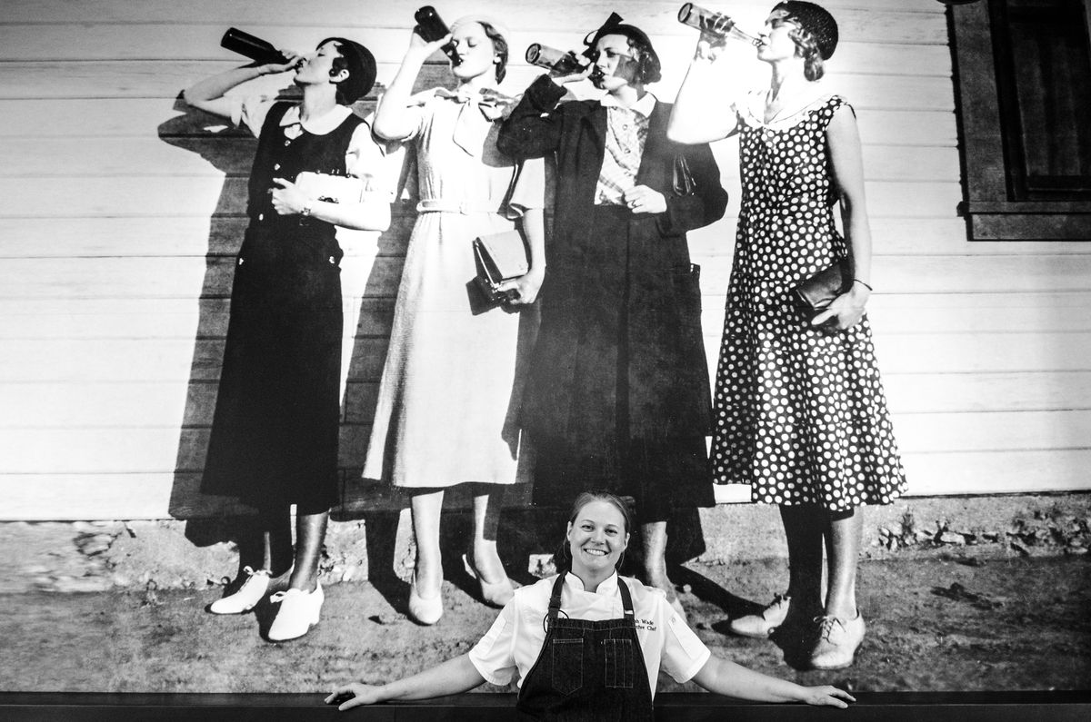 A black-and-white photograph of chef Sarah Wade, in chef's whites and an apron, smiling in front of a large old photograph of four women in dresses, drinking booze from bottles.
