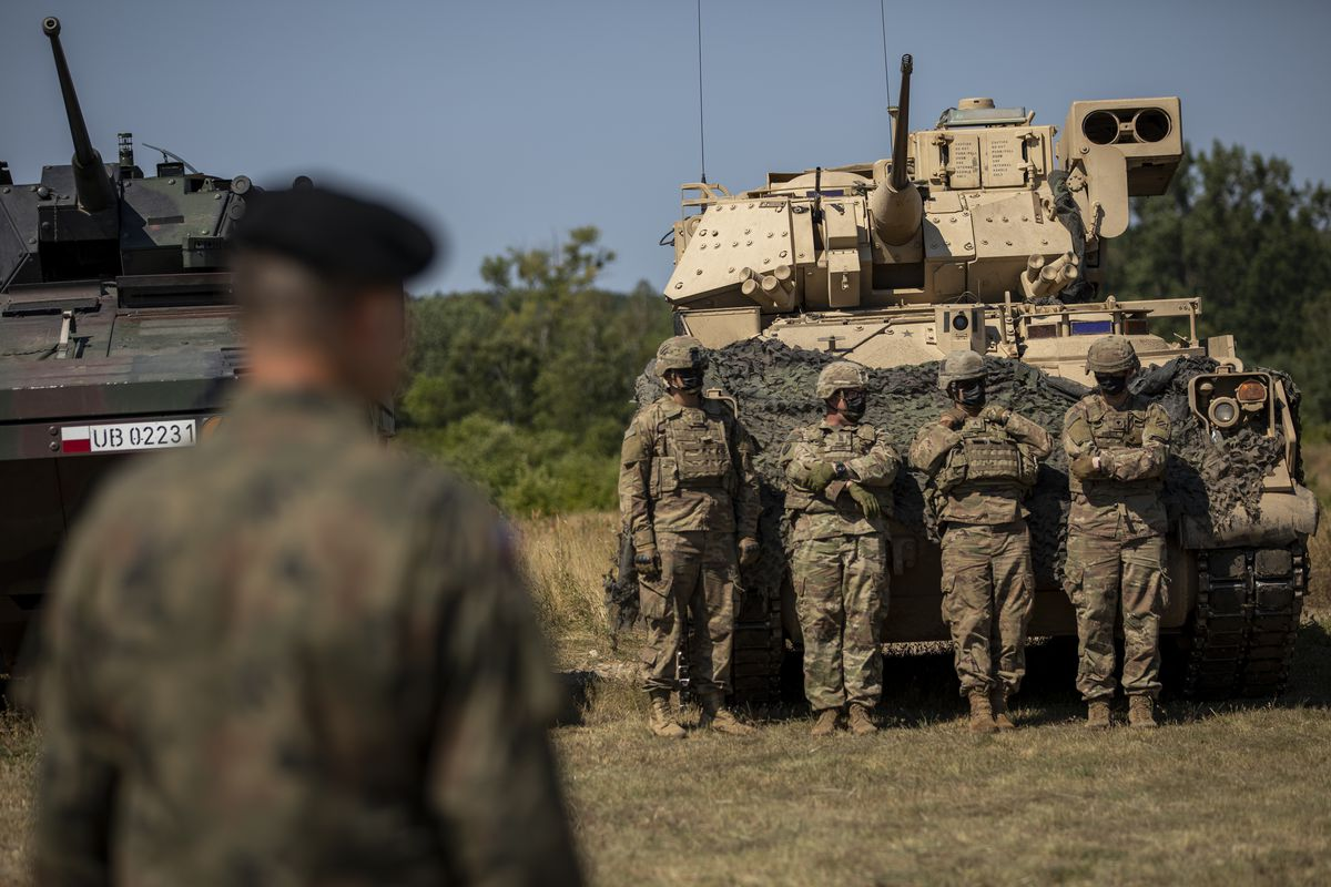 Soldiers in camouflage stand beside a tank.