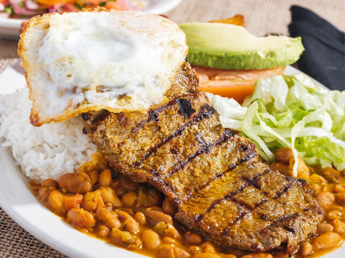 A large grilled steak over beans on a plate with fried eggs, shredded lettuce, and slices of avocado and tomato