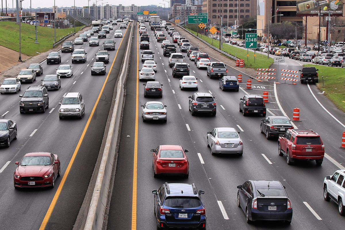 crowded highway with buildings in backround