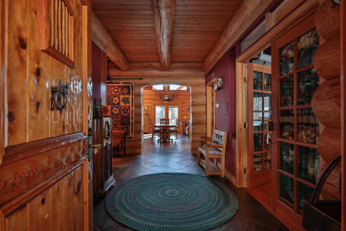 An entryway with French doors to the right and an archway leading to a living area on the end. All walls are wood grain or logs.
