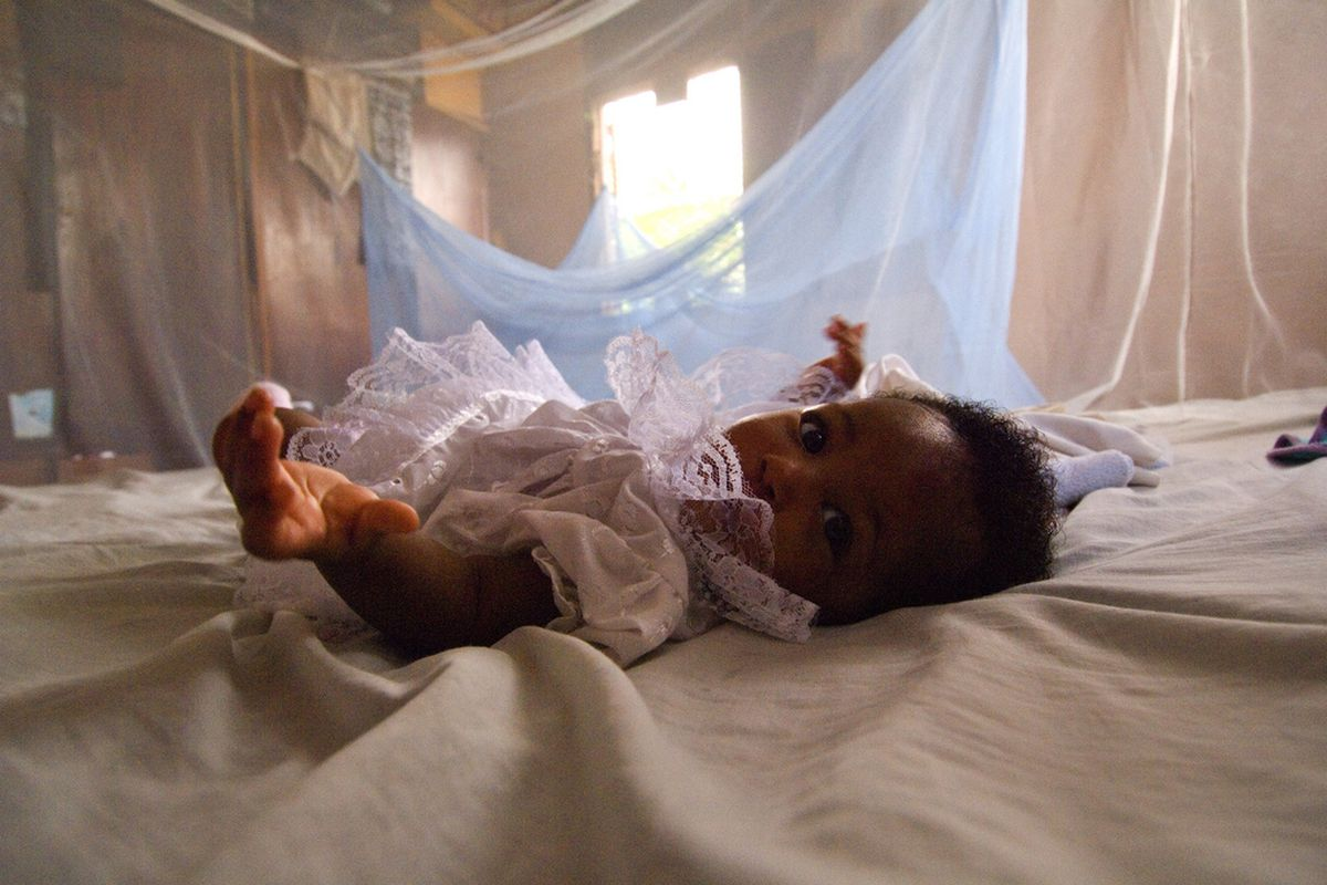 Infant surrounded by malaria bed net