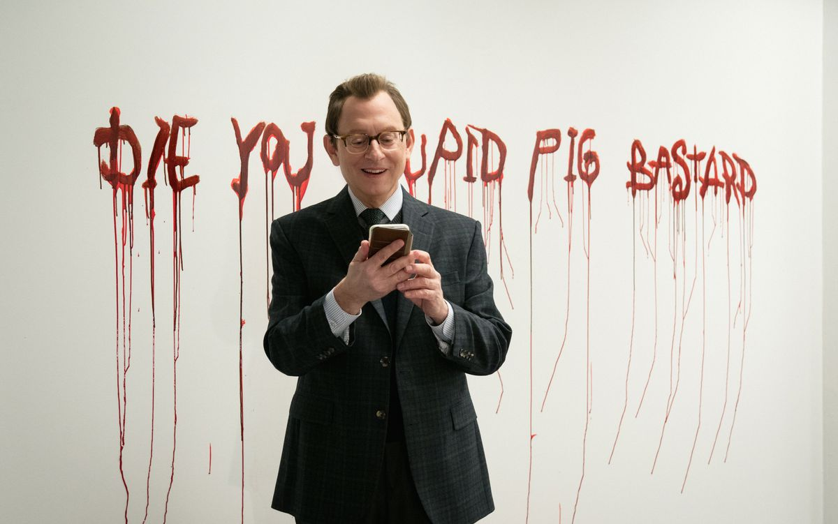 """Dr. Leland Townsend (Michael Emerson) takes a grinning selfie in front of a message — """"die you stupid pig bastard"""" — scrawled in blood on a wall in Evil season 2"""