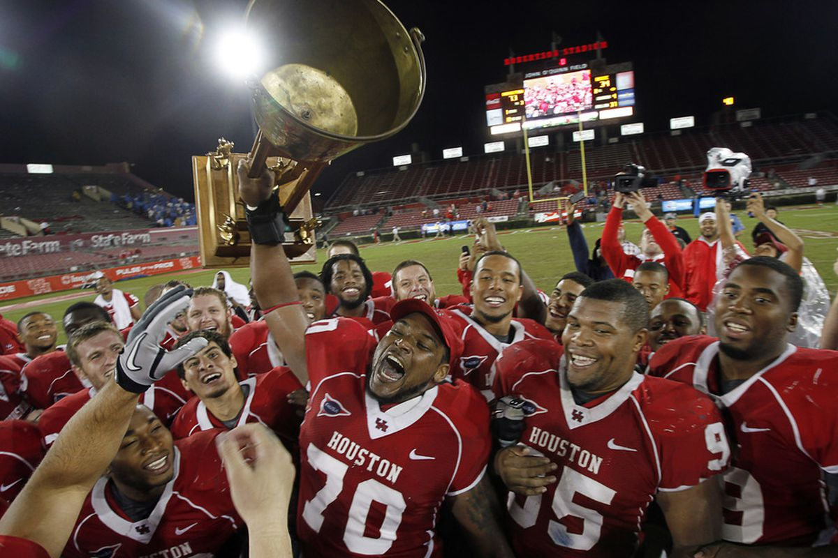 HOUSTON - OCTOBER 27:  Chris Thompson #70 of the Houston Cougars along with his teammates hold up the Bayou Bucket after they defeated the Rice Owls 73-34 at Robertson Stadium on October 27, 2011 in Houston, Texas.  (Photo by Bob Levey/Getty Images)