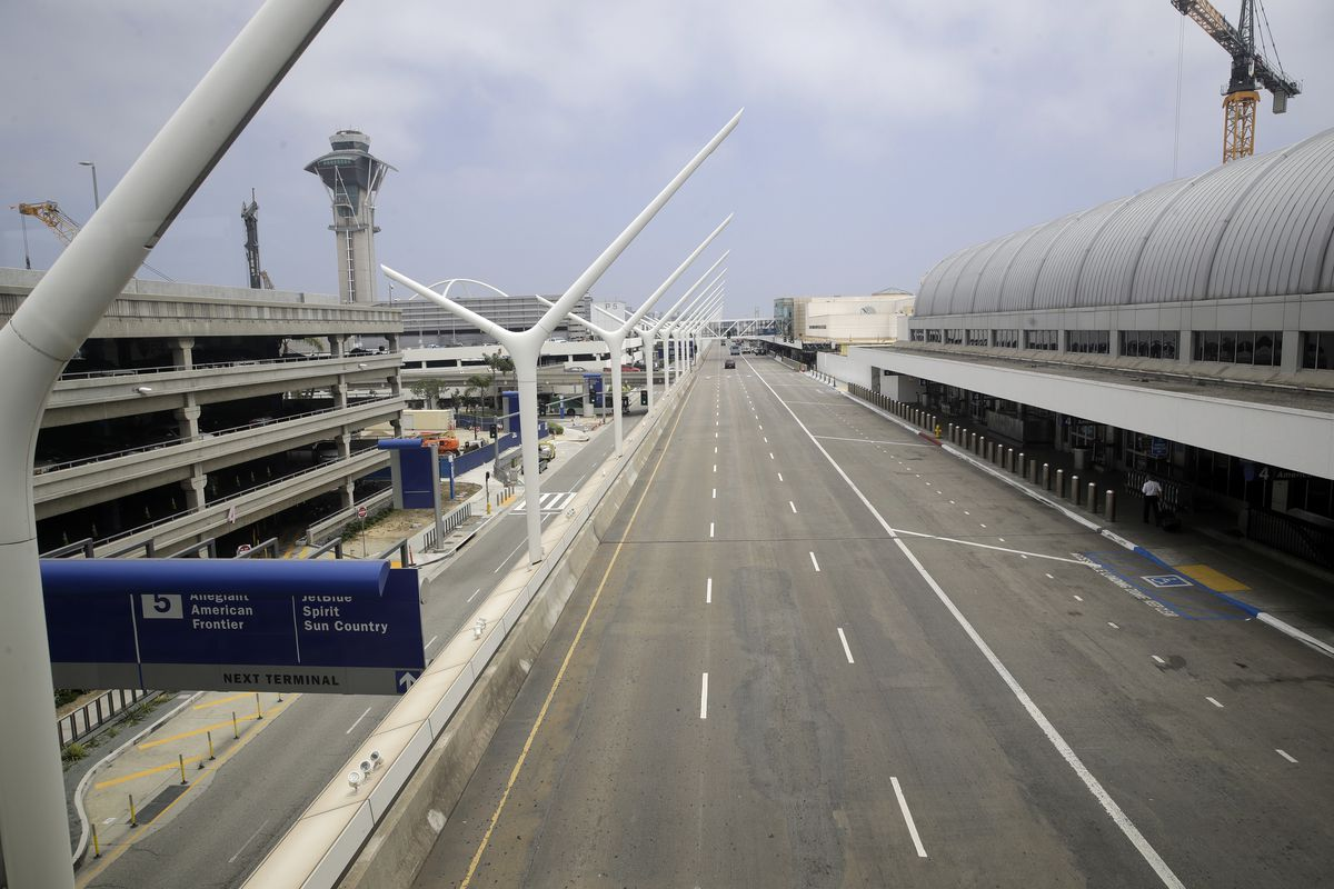 A empty street is seen at the Los Angeles International Airport Thursday, May 28, 2020, in Los Angeles. From Britain's EasyJet to American and Delta in the U.S., airlines are cutting even more jobs to cope with a crushing drop in air travel caused by the coronavirus.