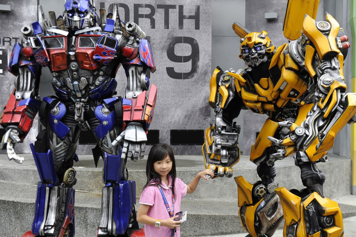 Two of Michael Bay's teaching assistants pose with a young woman in Singapore.