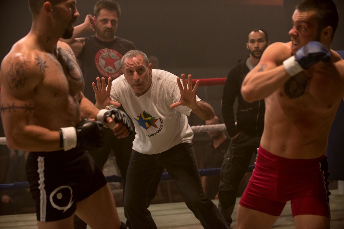 a gray-haired man in a white T-shirt and dark jeans (Isaac Florentine) holds up his hands while he stands between two boxers in a ring