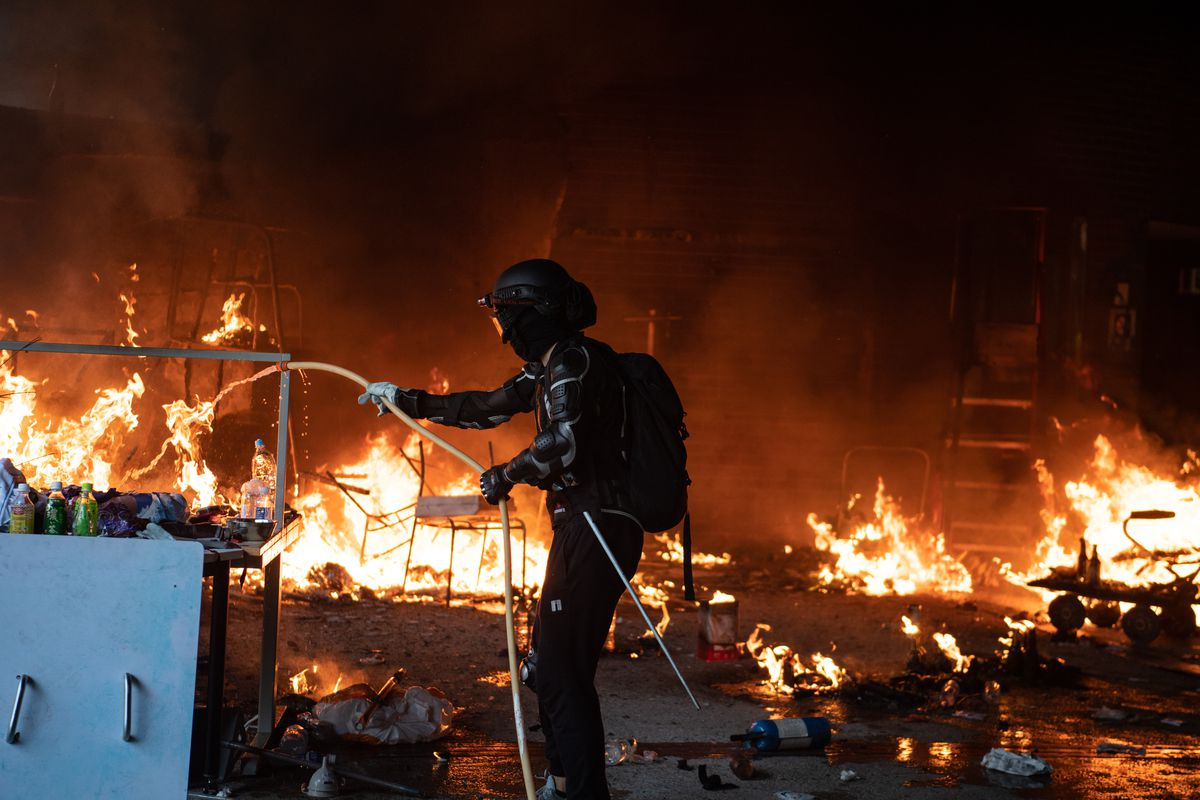An anti-government Hong Kong protester uses a garden hose to try to extinguish a room on fire.